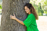 Beautiful environmentalist embracing tree trunk