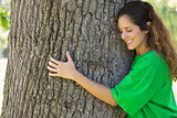Environmentalist hugging tree trunk