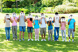 Multiethnic friends holding smileys in park