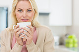 Portrait of a beautiful woman with coffee cup in kitchen