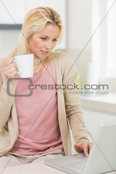 Beautiful woman with coffee cup using laptop in kitchen