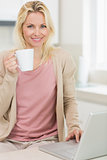 Beautiful woman with coffee cup using laptop in the kitchen
