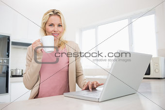 Portrait of beautiful woman with coffee cup using laptop in kitchen