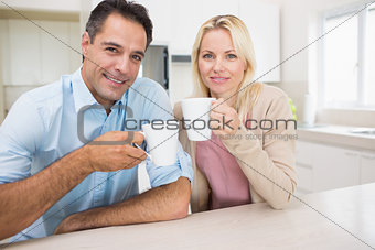 Portrait of happy couple with coffee cups in kitchen