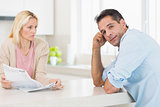 Upset couple with newspaper sitting in kitchen