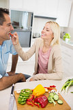 Happy loving woman feeding man vegetable in kitchen
