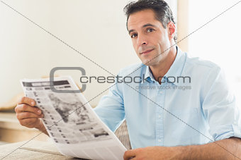 Casual man with newspaper looking away in kitchen