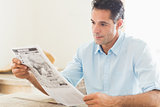 Serious casual man reading newspaper in kitchen