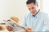 Smiling casual man reading newspaper in kitchen