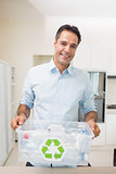 Smiling man carrying recycling container in kitchen