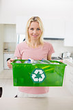 Smiling woman carrying recycling container in the kitchen