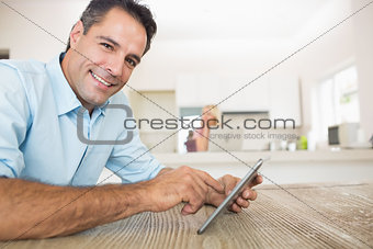 Portrait of smiling man using digital table in kitchen
