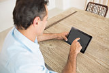 Concentrated man using digital table in kitchen