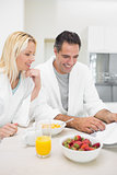Couple having breakfast while reading newspaper in kitchen