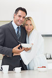 Portrait of a woman embracing well dressed man in kitchen