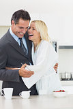 Cheerful woman embracing well dressed man in kitchen