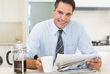 Smiling well dressed man with coffee cup and newspaper in kitchen