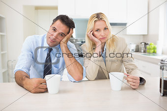 Portrait of well dressed couple  with coffee cups in kitchen
