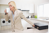 Well dressed woman drinking coffee while holding briefcase in kitchen