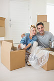 Smiling couple unpacking boxes in a new house