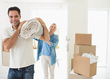 Smiling couple carrying rolled rug after moving in house