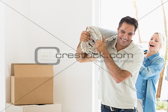 Couple carrying rolled rug after moving in a house