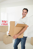Cheerful man carrying boxes in a new house