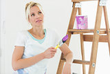 Beautiful woman with paint brush looking away in new house