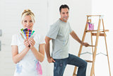 Couple with color swatches and ladder in a new house