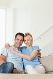 Portrait of a loving couple sitting on sofa in living room