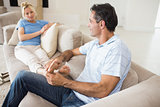 Relaxed couple sitting on sofa in living room