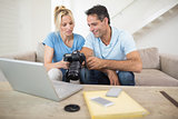 Couple with camera and laptop on sofa in living room