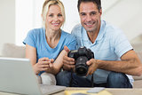 Happy couple with camera and laptop on sofa in living room