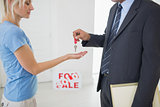 Real estate agent passing house key to woman