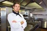 Serious male cook with arms crossed in kitchen
