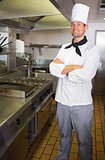 Smiling male cook with arms crossed in the kitchen