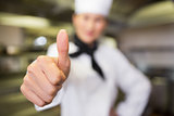 Blurred female cook gesturing thumbs up in kitchen