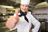Smiling female cook gesturing thumbs up in kitchen