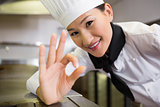 Smiling female cook gesturing okay sign in kitchen