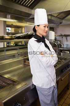 Thoughtful female cook standing in kitchen