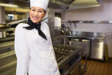 Smiling female cook standing in kitchen