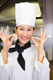 Closeup of smiling female cook gesturing okay sign