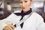 Confident female cook holding knife in kitchen