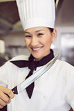 Smiling female cook holding knife in kitchen