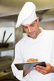 Male cook using digital tablet in kitchen