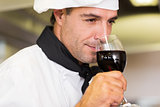 Closeup of a male chef smelling red wine