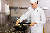Concentrated female chef preparing food in kitchen