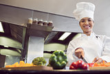 Smiling female chef cutting vegetables in kitchen