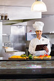 Female chef using digital tablet while cutting vegetables in kitchen