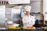 Smiling female chef with cut vegetables in kitchen